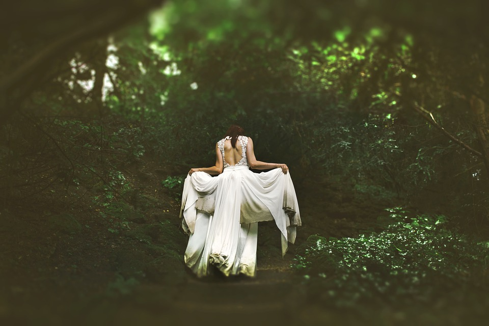 Woman in wedding dress in forest