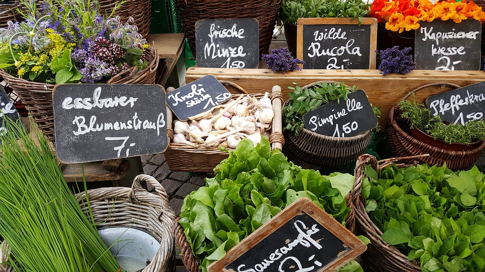 farmers market stand with vegetable prices
