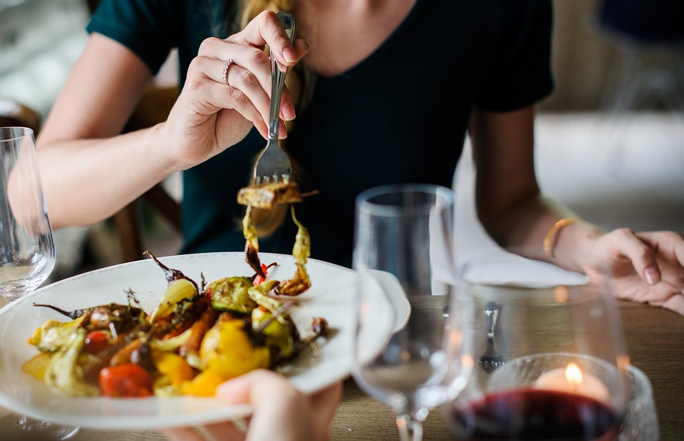 Woman eating a vegetable dish with a fork