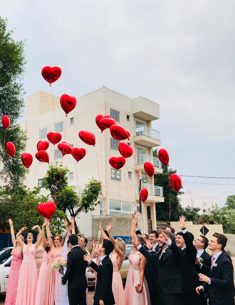 young people and balloons in shape of heart
