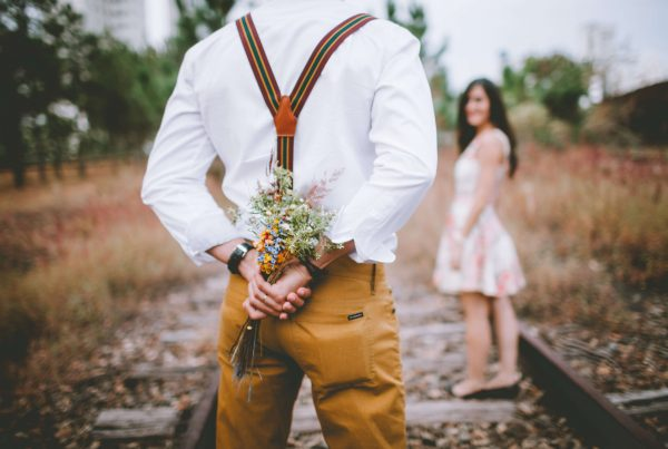 young man holding bouquet behind his back on railroad