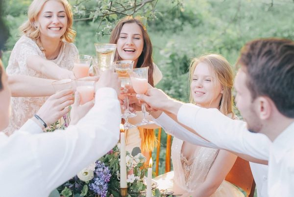 young people toast at the table in the garden