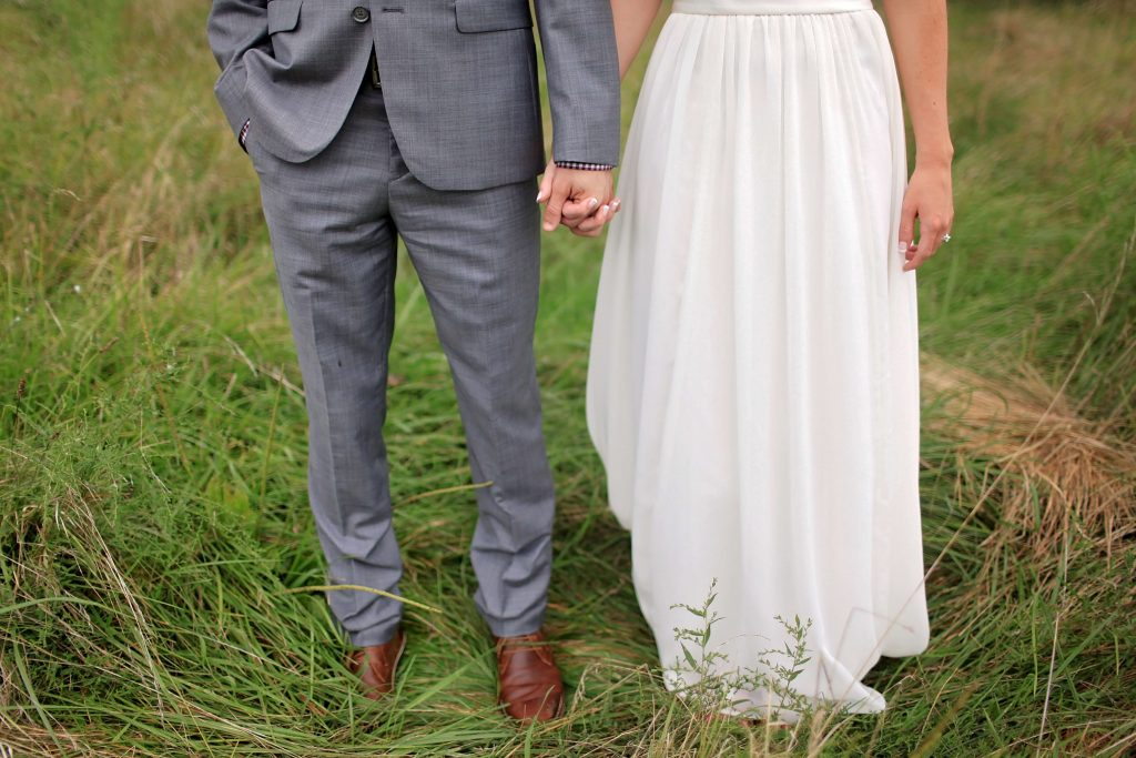 bride and groom standing on the grass and holding hands