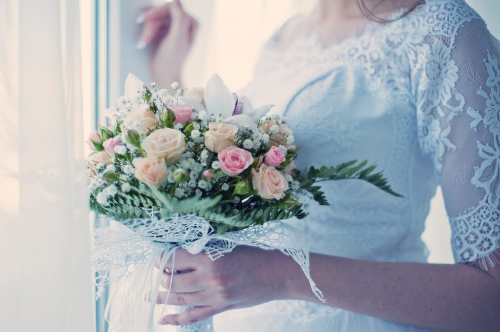 bride holding pink rose bouquet
