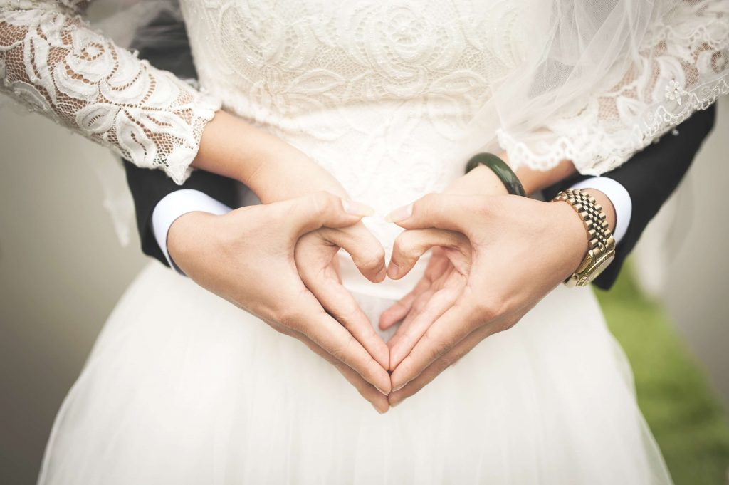 bride and groom make heart with their hands