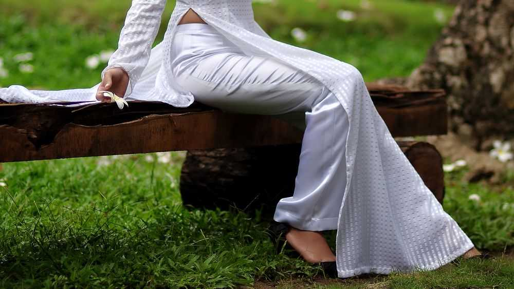 girl in white pants sitting on bench