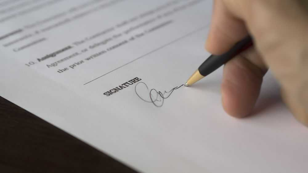 hand with pen sign document