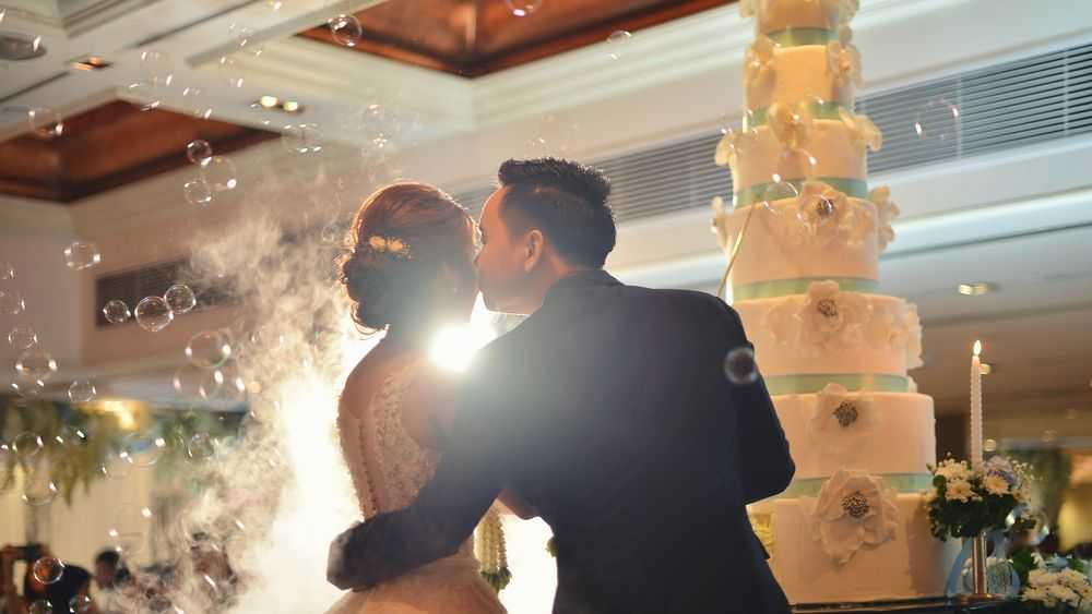 newlyweds kissing in front of wedding cake