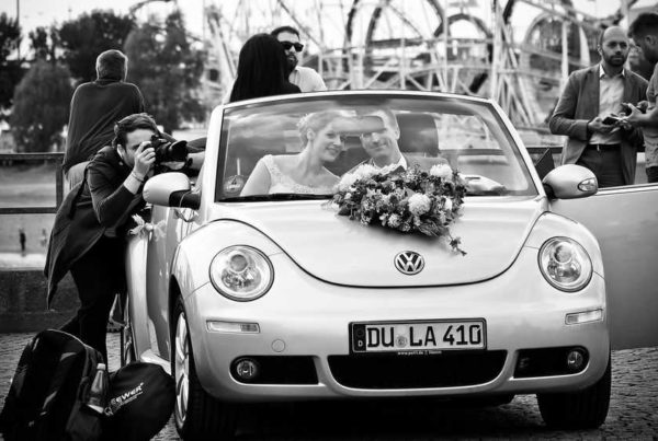 photographer taking photo of bride and groom in car
