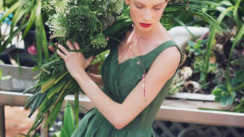 beautiful girl in green dress holding flowers