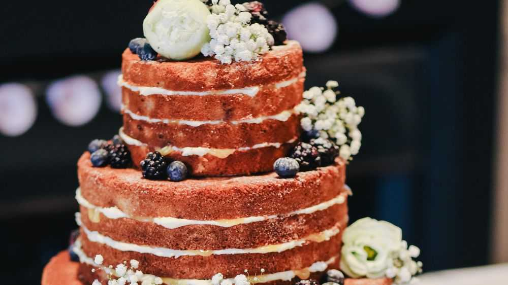 brown naked cake with fruits and flowers
