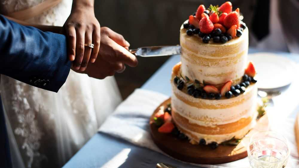 couple cutting naked wedding cake with fruits