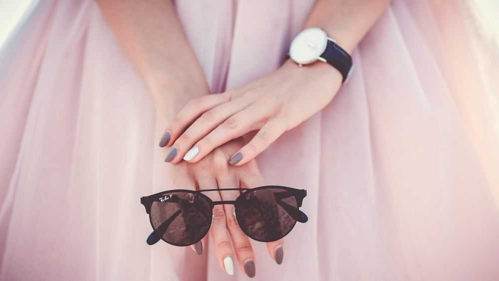 girl in pink dress holding sunglasses