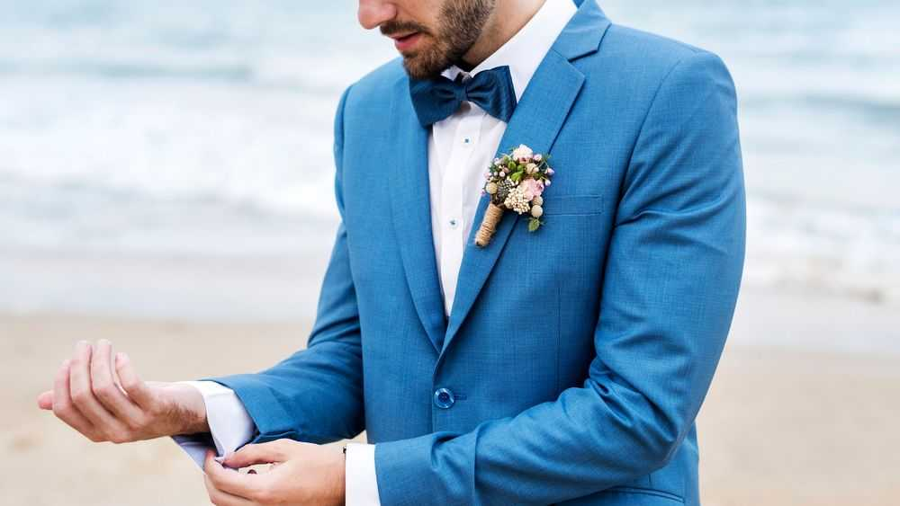 groom adjusting cuff on the beach