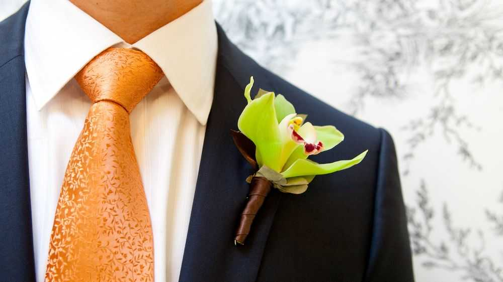 groom with orange tie and orchid boutonniere