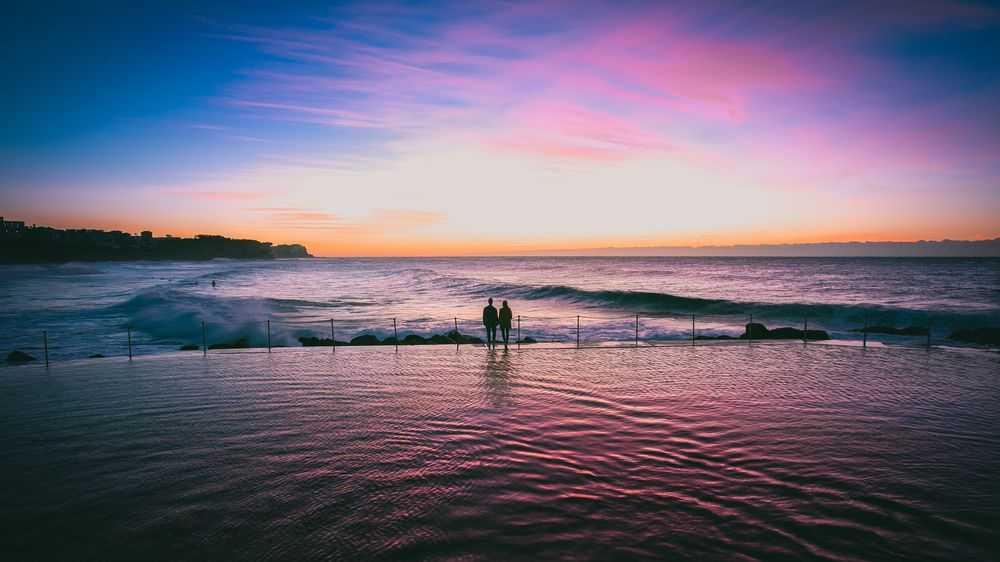 young couple walk along the coast