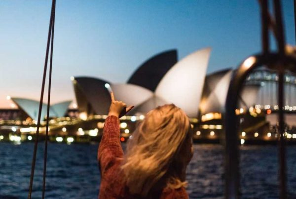 young woman pointing at Sydney Opera House