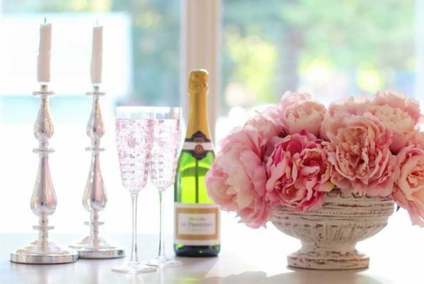 champagne bottle candles glasses and pink flowers on the table