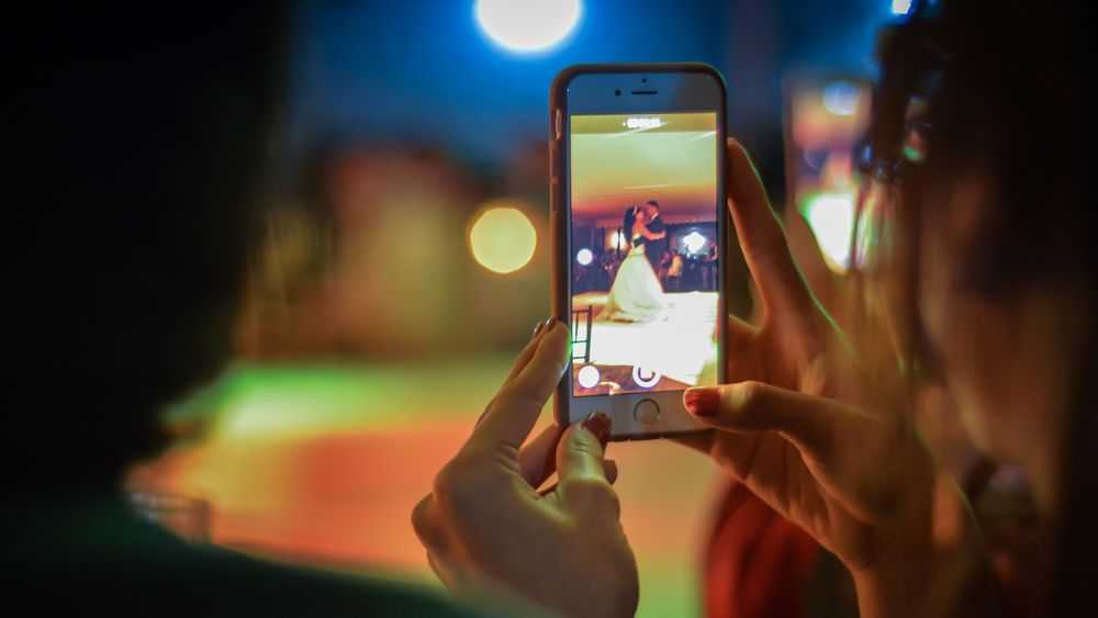 girl holding mobile phone and shooting wedding