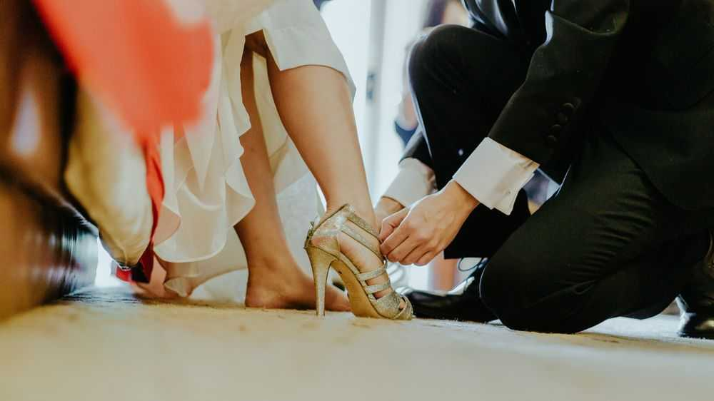 Man Putting on a Shoe on a Bride's Foot