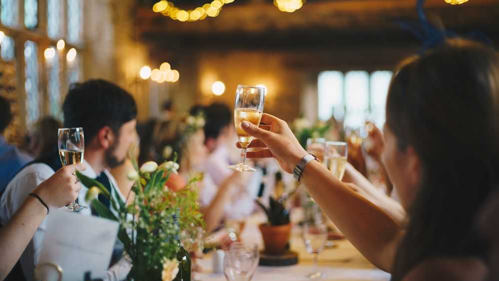 people with raised glasses wedding toast