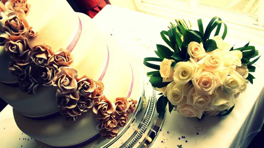 Wedding Cake On The Table And Bouquet Of Roses