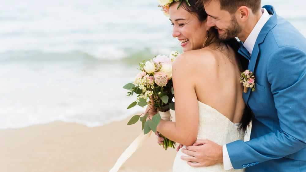 happy bride and groom on beach