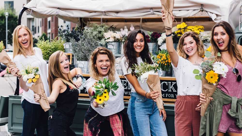 beautiful girls next to flower stand