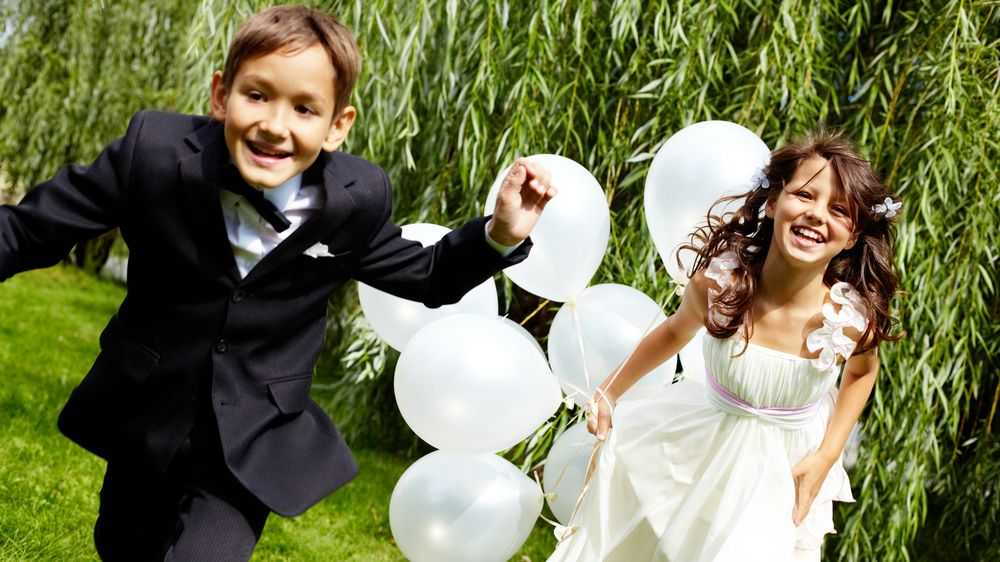 boy and girl running outside with balloons