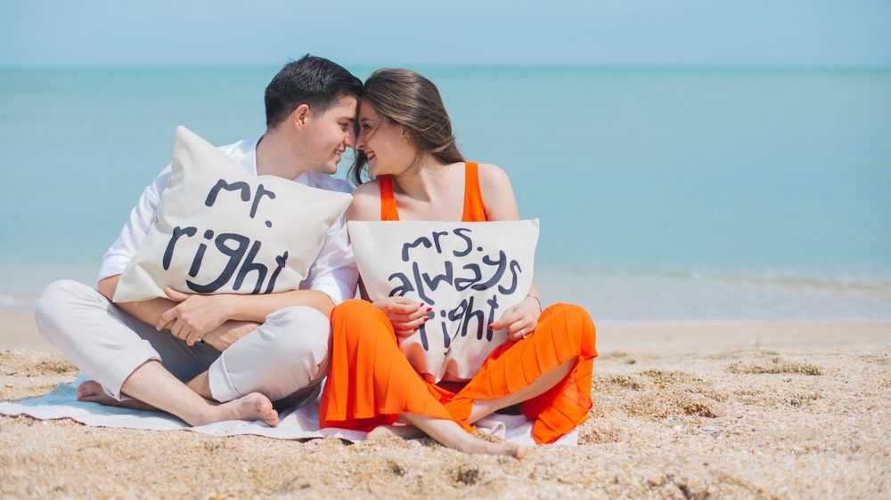 couple on the beach hugging pillows