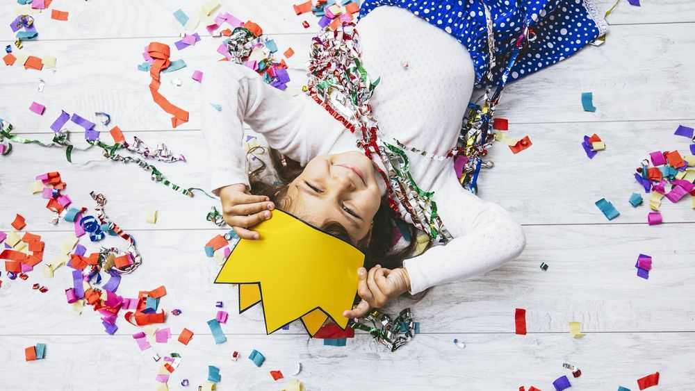 little girl laying on the floor with confetti and paper crown