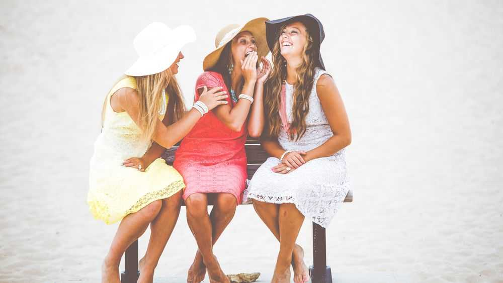 three young women sit on the bench and laugh